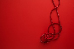 Decorative rose and beads on red background. Flat lay