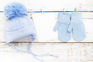 Small baby gloves, cap blank card on white wooden background. Flat lay. Top view