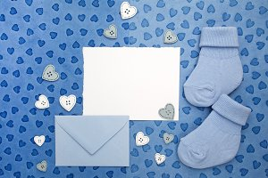 Small boy socks, blank card and evelop on blue wooden background. Flat lay.