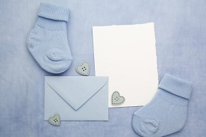 Small boy socks, blank card and evelop on blue fabric background. Flat lay.