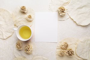 Cup of tea, dry flowers and blank card on white background. Free space for text. Top view