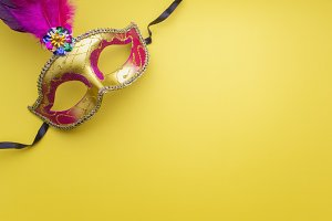 Colorful mardi gras or carnivale mask on a yellow background. Venetian masks. top view.