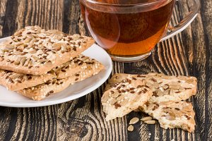 crispy bread with seeds of sunflower, flax and sesame seeds with a cup of tea on a dark wooden background