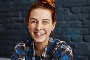 Close up portrait of beautiful young woman with ginger hair and clean healthy skin looking at camera with cheerful expression, happy with some positive news. Human face expressions and emotions