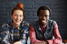 Cute interracial couple relaxing indoors, sitting against black brick wall background. Two stylish young friends of different races having nice time together, looking and smiling cheerfully at camera