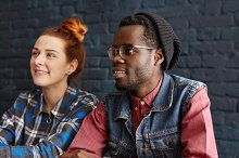 Friendhip and people concept. Beautiful young redhead Caucasian female with hair bun relaxing at coffee shop with modern interior together with her attractive dark-skinned boyfriend in trendy clothes