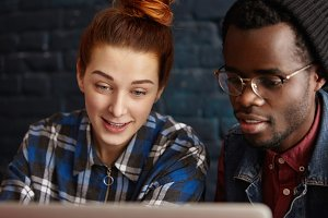 Cheerful Caucasian girl and African man in glasses and hipster hat watching video online, looking at laptop screen with amazed expression. Interracial couple surfing internet at cafe during lunch