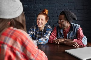 African man wearing hipster black hat and glasses and pretty girl with ginger hair talking to their common female friend in red checkered shirt, having nice time together during breakfast at cafe
