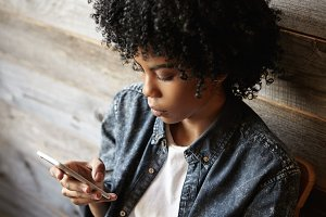 Close up shot of fashionable African girl with stylish Afro haircut wearing denim shirt sitting at cafe, using free wireless internet connection on cell phone, messaging online via social networks