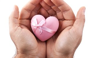 Pink heart in male hands on a white background.