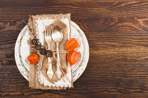 Tableware with orange Physalis and silverware