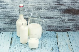 Jar and bottles with milk, and full glass with milk