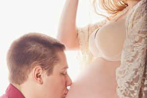 Man kissing belly of pregnant girl