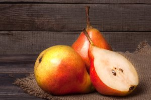 two pears with half on a dark wooden background