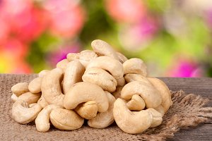 heap of cashew nuts on a wooden table with sacking and blurred garden background