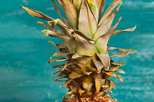 Pineapple is on the table a blue wooden background close-up
