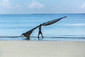 Africa Mombasa fisherman walking on the beach with a sail for a