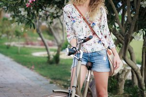 Blonde girl with bicycle near oleanr flowers