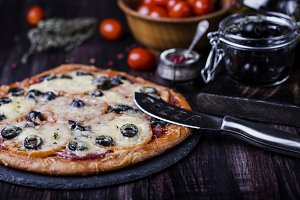 pizza with salami, mozzarella, olives and basil