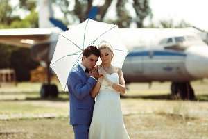 Groom and a bride with an umbrella