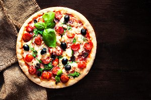 Hot pizza with Pepperoni Sausage on a dark background, top view.  Pizza on the black table with copy space.