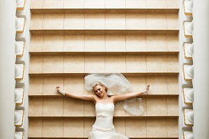 Happy bride lies on the stairs