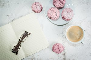 Notepad, coffee and pink cakes