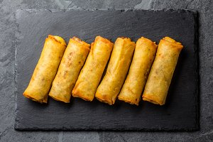 Fried spring rolls on slate plate. Top view