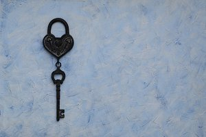 iron key from the lock lying on wooden vintage background, top view