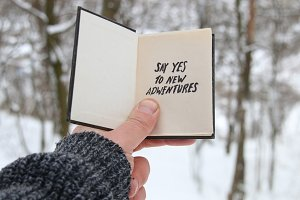 Hand holding a book with the inscription Say yes to new adventures on the background of the winter forest