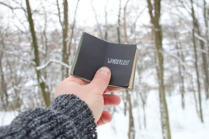 Wanderlust. Hand holding a book with the inscription on the background of the winter forest