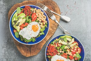 Healthy breakfast bowls with fried egg, chickpea sprouts, seeds, vegetables