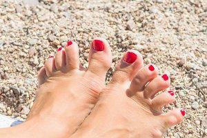 female feet in the sand