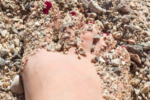 female feet in the sand