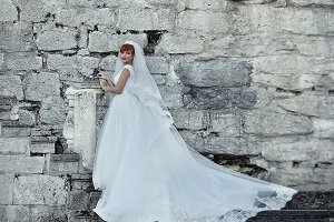 The bride stands near wall