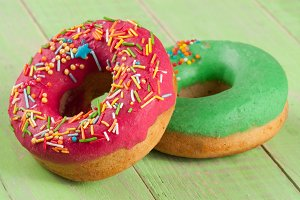 two glazed donut on wooden green background