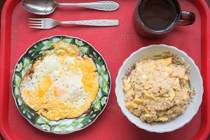 Overhead view. Scrambled eggs, tea, oatmeal with apples, banana, spoon, fork on a tray.