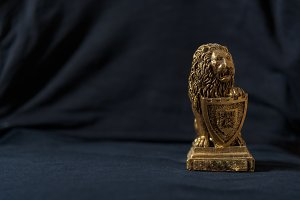 Statuette of golden lion leaning on shield. Black background.