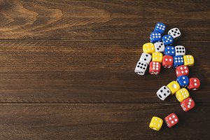 Dice of various colors on wooden table. Horizontal shoot.