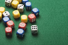 Dice white with number six and several dice of colors on green background. Horizontal shoot.