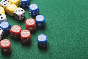 Dice blue with number six and several dice of colors on green background. Horizontal shoot.