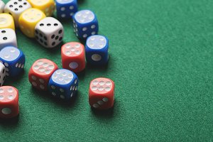 Dice red with number six and several dice of colors on green background. Horizontal shoot.