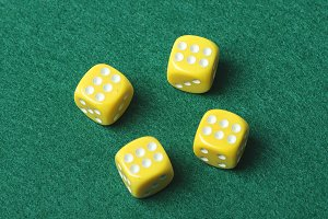 Four yellow dice with number six on green background. Horizontal shoot.