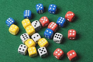 Dice of various colors on green background. Horizontal shoot.