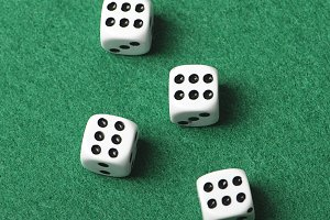 Four white dice with number six on green background. Horizontal shoot.