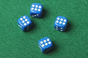 Four blue dice with number six on green background. Horizontal shoot.