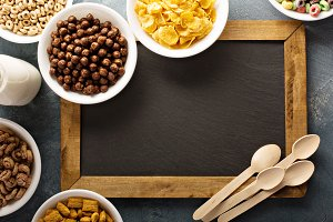 Variety of cold cereals in white bowls around chalkboard