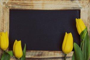 Beautiful yellow tulips with blackboard