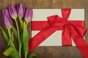 Purple tulips bouquet and gift card on wooden background
