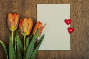 Orange tulip flowers and blank greeting card on wooden background